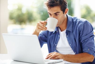 Portrait of a young man drinking coffee while looking at the laptop