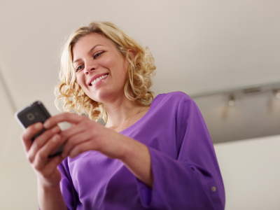 Young beautiful caucasian blonde woman typing e-mail message on smartphone and laughing. Low angle view, copy space