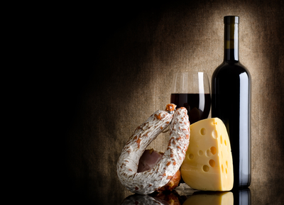 Wine bottle and cheese on a background of old canvas